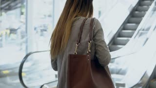 Young beautiful woman going to work in modern office building. Businesswoman going up on escalator and using smartphone.