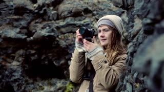 Young beautiful woman holding camera and taking photos in the mountains. Traveling female filming on the nature.