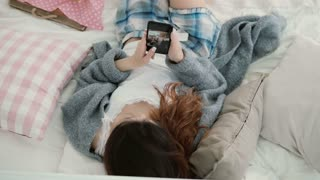 Young beautiful woman lying on the bed and holding mobile phone. Girl watches photos on smartphone and drinks juice.