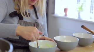 Young beautiful woman making the colored cream for desserts, mixing ingredients in a bowl. Female cooking in the kitchen