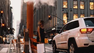 Young beautiful woman standing in downtown with shopping bag of New York, America near the smoke pipe, steam of fog.