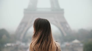 Young beautiful woman standing near the Eiffel tower in Paris, France, turning and looking at camera and smiling.