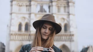 Young beautiful woman standing near the Notre Dame in Paris, France and taking photos on retro film camera.