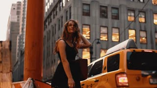 Young beautiful woman standing near the traffic road in New York, America after shopping and waiting for a taxi.