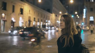 Young beautiful woman standing near the traffic road in the evening and looking around, find the way in smartphone.
