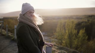 Young beautiful woman standing on the bridge in cold sunny day and enjoying the landscape. Hairs waving on the wind.