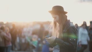 Young beautiful woman standing on the street full of people and using smartphone. Stylish female in city on sunset.