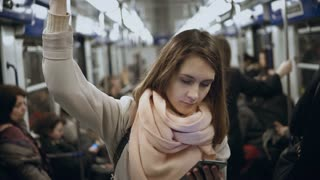 Young beautiful woman uses the smartphone in public transportation, in metro. Girl surfing the Internet.