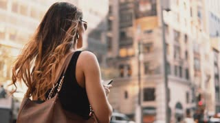 Young beautiful woman walking in downtown of New York, America, looking around and using smartphone.