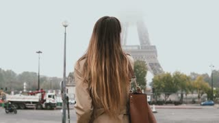 Young beautiful woman walking in foggy morning near the Eiffel tower in Paris, France and talking on mobile phone.