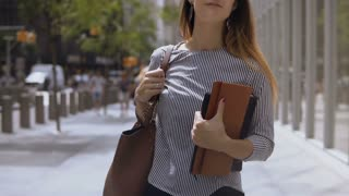 Young beautiful woman walking in street. Stylish businesswoman holding documents and going to work. Slow motion.