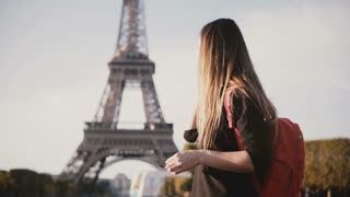 Young beautiful woman with backpack standing near the Eiffel tower and talking on mobile phone, sharing impression.