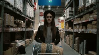 Young beautiful woman with cart full of goods walking through the high shelves with things for repair in big warehouse.