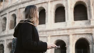 Young beautiful woman with map standing near the Colosseum in Rome, Italy and try to find way, because she lost.
