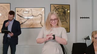 Young blonde woman going through the modern office and looking on the smart watch. Girl uses new technology. Slow motion