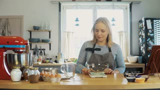 Young blonde woman using the kitchen scales to weighing the flour. Beautiful female baking the cupcakes on the kitchen.