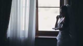Young bride staying near the window and drinking coffee in morning. Woman with veil getting ready to wedding ceremony.