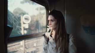 Young brunette traveling by train. Attractive girl looking at window to landscape outside, doing up the hair.