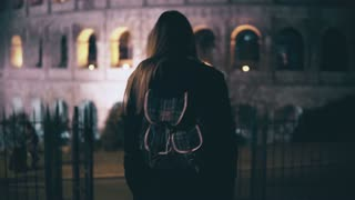 Young brunette woman comes downstairs opposite to the Colosseum in Rome, Italy. Girl walking in the city late at night.