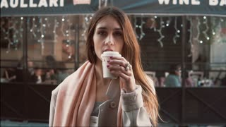 Young brunette woman with cup of coffee standing in front of show-window. Girl dreaming to buys clothes. Slow motion.