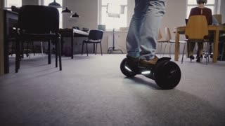Young businessman using gyroscooter to move around the office. Confident business leader guides colleagues, close-up 4K.
