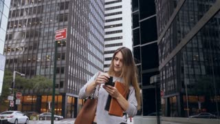Young businesswoman walking through the financial district of New York, America and talking on mobile phone. Slow motion