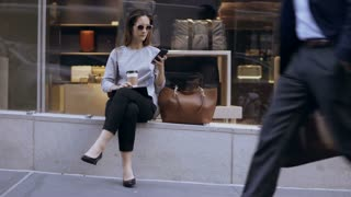 Young busy businesswoman sitting near the shop-window with cup of coffee and using smartphone in crowded place.