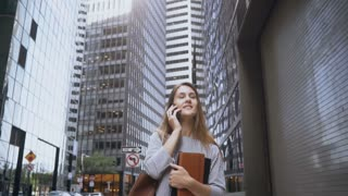 Young busy businesswoman talking on mobile phone and going to work through the financial district in New York. Slow mo.