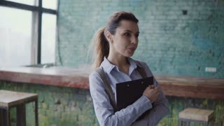 Young caucasian woman in modern coworking space. Portrait of beautiful female holds the documents, points with pencil.