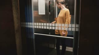 Young confident European woman pushes elevator button, door closes and she rides down, view through a glass wall.
