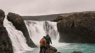 Young couple hiking in Iceland. Traveling man and woman standing near the powerful waterfall and raising hands.