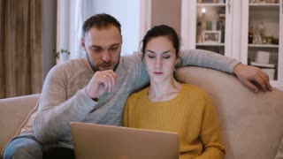 Young couple sitting on the couch and holding computer. Man and woman using laptop while sitting at living room.