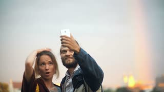 Young couple taking selfie photos with rainbow on background. Cheerful man and woman use the smartphone technology.