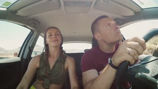 Young couple traveling in the car through the rocks. Man and woman have fun, making funny face on the road together