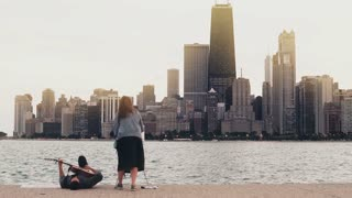 Young creative couple on the shore of Michigan lake, Chicago, America. Woman draw, ma play guitar lying on shore.