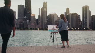 Young creative couple on the shore of Michigan lake, Chicago, America. Woman drawing, man holding the guitar in evening