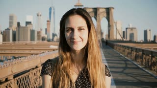 Young European beautiful traveler girl touching hair, looking at camera and smiling at Brooklyn Bridge, New York City 4K
