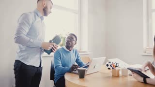 Young European boss motivates and encourages colleagues. Happy multiethnic workers smile, enjoy modern healthy office 4K