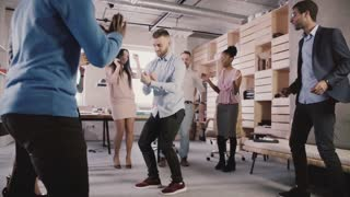 Young European businessman dancing in circle with colleagues at office party, celebrating career promotion slow motion.