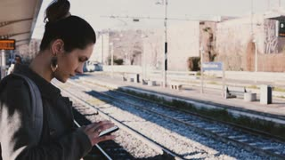 Young European businesswoman using smartphone on train station on a sunny day, looking around, nervous and late.