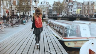 Young European lady walks talking on the phone. Free and easy relaxed walk along wooden river embankment with a boat. 4K