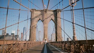 Young European romantic couple spin holding each other, run to camera holding hands at Brooklyn Bridge on a summer day.