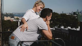 Young European woman listening to her man. Couple standing together at a small romantic sunny balcony in New York.