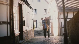 Young father holds two happy kids in his arms. Handsome European man with boy and girl waving hands and smiling. 4K.