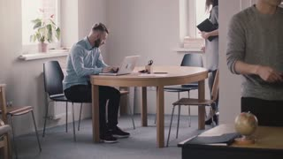 Young female boss in formal clothes comes up, sits down by male employee working with laptop to help in modern office.