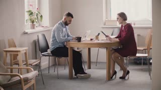 Young female boss sits by the table across male employee with laptop, shows him info on tablet in modern light office.
