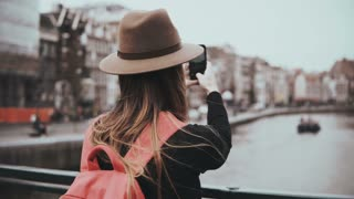 Young girl takes photos and talks on the phone. Beatiful woman journalist with long hair and red backpack working. 4K.