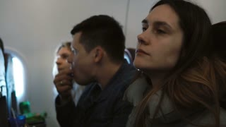 Young group of people traveling by plane together. Portrait of woman who have fear of heights. Friends going to the trip