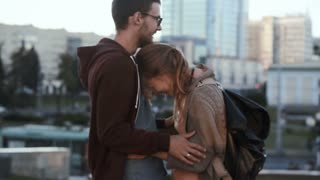 Young handsome couple standing in the city centre and hugging. Happy man and woman on a romantic date.
