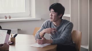 Young handsome happy Japanese man talking by the table, smiling at job interview in modern trendy light office.